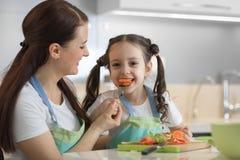 Légumes de alimentation de fille d'enfant de mère dans la cuisine Photographie stock