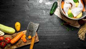 Légumes de coupe avec une hache au potage au poulet Photos libres de droits
