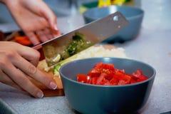 Légumes de coupe dans la cuisine Image stock