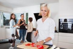 Légumes de coupe de femme sur le compteur Photographie stock
