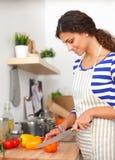 Légumes de coupe de jeune femme dans la cuisine à la maison Images stock