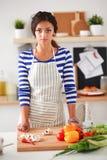 Légumes de coupe de jeune femme dans la cuisine à la maison Photos libres de droits