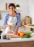 Légumes de coupe de jeune femme dans la cuisine à la maison Images libres de droits