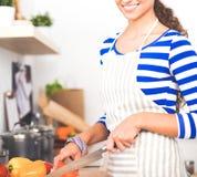 Légumes de coupe de jeune femme dans la cuisine à la maison image libre de droits