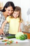 Légumes de découpage de petite fille avec sa mère photographie stock