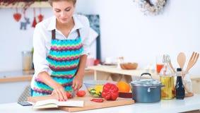 Légumes de découpage de jeune femme dans la cuisine Image stock