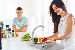 Légumes de lavage de femme dans l'évier et l'homme se tenant à côté He Photo stock
