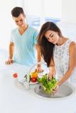 Légumes de lavage de femme dans l'évier et l'homme se tenant à côté He Image libre de droits