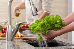 Légumes de lavage pour une salade Photos stock