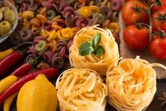 Légumes de pâtes, crus et mûrs, citron sur un fond en bois Ingrédients pour faire cuire les plats italiens Plan rapproché Photographie stock libre de droits