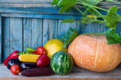 Légumes de récolte d'automne : potiron, pastèque, maïs, poivrons, aubergine, tomates sur une table en bois images libres de droits