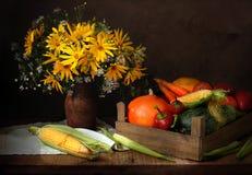 Légumes en boîte en bois et fleurs sur une table Images libres de droits
