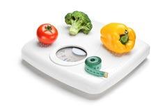 Légumes et bande de mesure sur une échelle de poids Photographie stock libre de droits