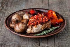 Légumes et bifteck grillés d'un plat d'argile Photographie stock