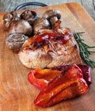 Légumes et bifteck sur une planche à découper Photos stock