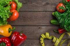 Légumes et dans la bande de mesure dans le régime sur le fond en bois Vue supérieure Photo libre de droits