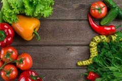 Légumes et dans la bande de mesure dans le régime sur le fond en bois Vue supérieure Images stock
