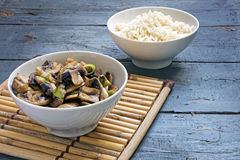 Légumes et riz dans des cuvettes sur un tapis en bambou et rustique de champignon Images stock