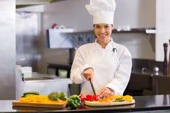 Légumes femelles de sourire de coupe de chef dans la cuisine Images libres de droits