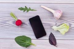 Légumes frais, assaisonnements et smartphone Photo stock
