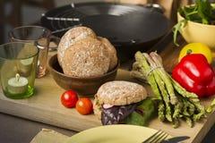 Légumes frais et petits pains dans une cuisine Photo stock