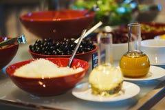 Légumes frais, herbes, olives, sauce et sauce salade au compteur photos stock