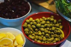 Légumes frais, herbes, olives, sauce et sauce salade au compteur photographie stock