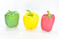 Légumes frais trois rouges doux, jaune, poivrons verts d'isolement Photographie stock