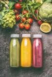 Légumes, fruits et smoothies organiques colorés verts, rouges et jaunes de baies avec des ingrédients dans des bouteilles sur la  Images stock