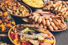 Légumes grillés et saucisses frites, un festival de nourriture douce de rue photos stock