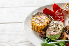 Légumes grillés sur l'espace libre blanc de plat Image stock