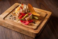 Légumes marinés un conseil en bois avec des concombres, ail, poivre de piment, et acidifie photos libres de droits