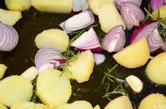 Légumes, oignons, pomme de terre rôtie et herbes faisant cuire au four dans le four Image stock