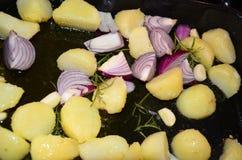 Légumes, oignons, pomme de terre rôtie et herbes faisant cuire au four dans le four Image libre de droits
