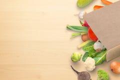 Légumes organiques frais dans le sac de papier sur la table de cuisine Image libre de droits