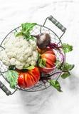 Légumes organiques frais - le chou-fleur, les tomates d'héritage, betteraves dans le vintage metal le panier sur le fond clair photos stock