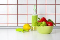 Légumes, pétrole et grattoir sur le fond de comptoir de cuisine photos libres de droits