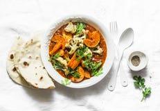 Légumes rôtis de cari Patates douces, chou-fleur, carottes, oignons, potiron avec de la sauce à cari sur le fond clair, vue supér photos stock