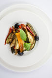 Légumes rôtis d'un plat blanc sur le fond de wwhite Photo stock