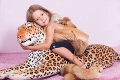 Léopard de petite fille et de jouet Photographie stock