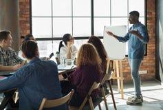 Líder afro-americano que fala seus empregados no escritório fotografia de stock royalty free