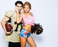 Líder da claque louro bonito da menina com espanador dos PP e um futebol americano do jogador do lançador que levanta com uma bol imagens de stock