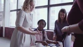 Líder da equipa africano novo que anda através do trabalho moderno do escritório e dos controles do empregado A fêmea olha os exe vídeos de arquivo