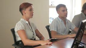 Líder da equipa caucasiano fêmea novo que preside a reunião da sala de reuniões com os colegas bem sucedidos do negócio video estoque