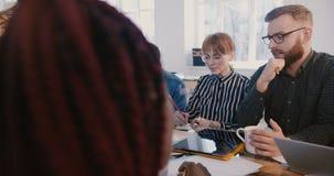 Líder da equipe fêmea seguro novo bem sucedido que motiva empregados multi-étnicos felizes da empresa na reunião moderna do e filme