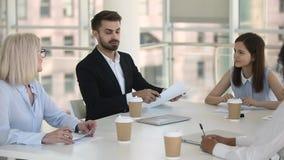 Líder da equipe ou participante de conferência masculino que fala na reunião de grupo video estoque