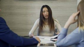 Líder da mulher que fala ao subordinado na reunião que senta-se no escritório video estoque