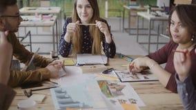 Líder de equipo de sexo femenino joven que habla con el pequeño grupo de personas multirracial Reunión de negocios de la empresa  almacen de metraje de vídeo