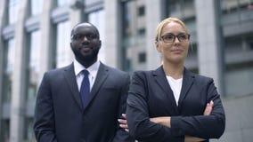 Líder de sexo femenino y subordinado que presentan para la cámara, hombres de negocios acertados almacen de metraje de vídeo