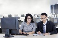 Líder de sexo masculino que ayuda a su socio en la oficina imagen de archivo